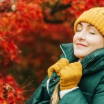 Autumn portrait of young beautiful woman wearing green jacket and set of yellow hat and gloves, posing next to bright red Japanese maple tree. Eyes closed